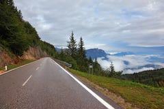 Nasse Straße in den Schweizer, niedrigen Kumuluswolken Lizenzfreie Stockfotos
