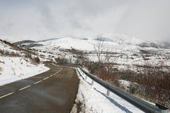 Nasse Straße in einem schneebedeckten Berg Lizenzfreies Stockbild