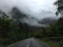 Nasse Straße mit Berg und Anlagen an einem regnerischen Tag Stockfotografie