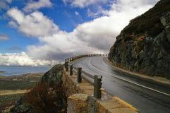 Nasse Straße zu den Bergen Stockfotos
