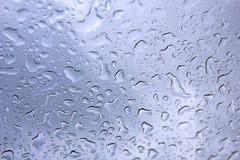 Nasse Tropfen am transparenten Glas Himmelreflexion stockbild