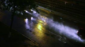 Nasser Asphalt im Regen, auf dem Autos fahren, Fokus auf dem Asphalt, in der regnerischen Straße in der Nachtstadt stock video footage