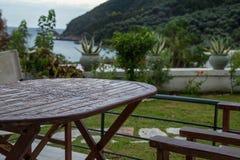 Nasser Holztisch nach Regen und eine Ansicht zu Lichnos setzen im Hintergrund, Parga auf den Strand Stockfotos