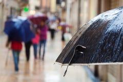 Nasser Regenregenschirm vor aus Fokusleuten heraus Stockfotos
