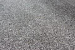 Nasser Straßenasphalt mit Felsen und rauer Beschaffenheit Stockbild