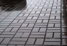 Nasses geometrisches Muster der städtischen Plasterung Lizenzfreies Stockfoto