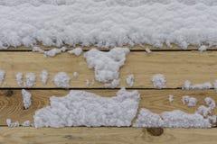 Nasses Holz und Schnee Stockfotos