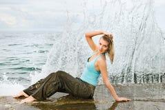 Nasses Mädchen, das nahe dem Ozean sitzt Stockfotografie