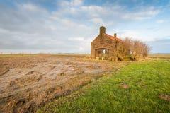 Nasses Stoppelfeld und ein verlassenes kleines Gebäude Lizenzfreies Stockfoto