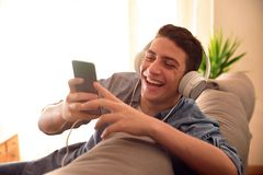 Nastolatek śmia się z smartphone opiera z tyłu leżanki obrazy stock