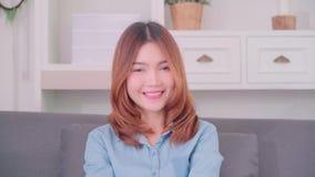 Nastolatek Azjatycka kobieta czuje szczęśliwy uśmiechniętego i patrzeje kamera podczas gdy relaksuje w jej żywym pokoju w domu zbiory wideo