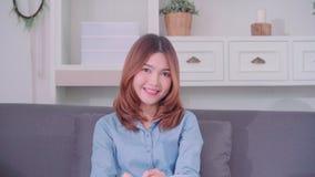 Nastolatek Azjatycka kobieta czuje szczęśliwy uśmiechniętego i patrzeje kamera podczas gdy relaksuje w jej żywym pokoju w domu zdjęcie wideo