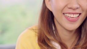 Nastolatek Azjatycka kobieta czuje szczęśliwy uśmiechniętego i patrzeje kamera podczas gdy relaksuje w jej żywym pokoju w domu zbiory