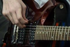 Nastolatek bawić się gitarę elektryczną Palce młody basista ciągną basowych sznurki muzykalny temat Zakończenie zdjęcia stock