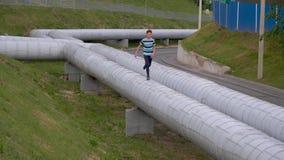 Nastolatek biega przez drymb grzejna magistrala zdjęcie wideo