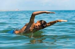 Nastolatek chłopiec cieszy się pływać w morzu Obrazy Royalty Free