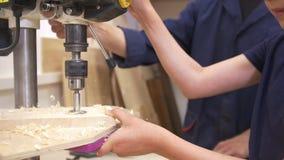 Nastolatek chłopiec musztruje dziury na drewnianej desce używać przemysłowego wyposażenie w ciesielka warsztacie zdjęcie wideo