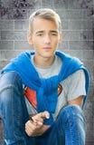 Nastolatek chłopiec obsiadanie przy ściennym zbliżeniem zdjęcia royalty free