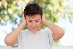 Nastolatek chłopiec plenerowy nakrycie jego ucho obrazy royalty free