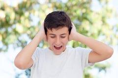 Nastolatek chłopiec plenerowy nakrycie jego ucho obrazy stock