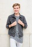 Nastolatek chłopiec uśmiechnięty portret stoi nad betonowym tłem Fotografia Royalty Free