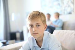 Nastolatek chłopiec siedzi samotnie na kanapie Fotografia Stock