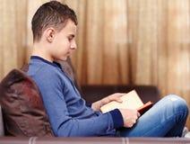 Nastolatek czyta książkę Zdjęcia Royalty Free