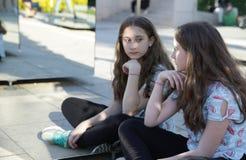 Nastolatek dziewczyna odbijał w lustrze z poważnym twarzy obsiadaniem w lotosowej pozycji w parku obraz royalty free