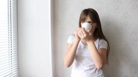 Nastolatek dziewczyna pije gorącej herbaty przy okno i ono uśmiecha się zdjęcie wideo