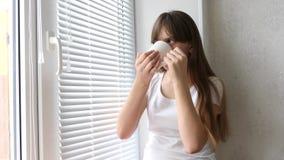 Nastolatek dziewczyna pije gorącej herbaty przy okno i ono uśmiecha się zbiory