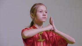 Nastolatek dziewczyna robi kung fu wita dwa ręki wraz z prawą pięścią na lewej palmie jest Wushu Tai Chi chińczykiem zdjęcie wideo