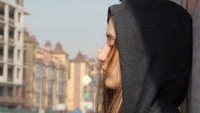 Nastolatek dziewczyna w hoody z kapiszonem dalej, luźnym stubarwnym włosy przeciw graffiti i, unfocused zielony ruch drogowy zbiory