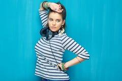 Nastolatek dziewczyny portret na błękit ścianie z powrotem Zdjęcia Stock