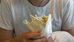 Nastolatek je du?? kurczak rolk? w fast food kawiarni Na stole s? wielcy cheeseburgers i francuz?w d?oniaki zdjęcie wideo