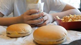 Nastolatek je du?? kurczak rolk? w fast food kawiarni Na stole s? wielcy cheeseburgers i francuz?w d?oniaki zbiory