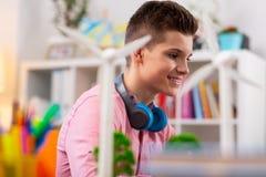 Nastolatek jest ubranym błękitne słuchawki na szyi studiowania ekologii obrazy stock
