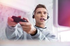 Nastolatek jest ubranym czarne słuchawki z mikrofonem bawić się gra wideo zdjęcia royalty free