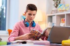 Nastolatek jest ubranym słuchawki na szyi obsiadaniu przy studiowaniem i laptopem zdjęcie royalty free