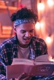Nastolatek jest w ten sposób skeptical co on czyta w książce go bierze przed pora snu zdjęcie royalty free