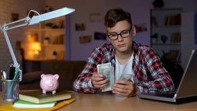 Nastolatek liczy dolarowych rachunki i stawia one piggyback, pierwszy pensja zdjęcie stock