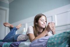 Nastolatek nastoletnia dziewczyna texting na smartphone lying on the beach w łóżku w domu obrazy stock