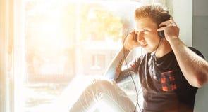 Nastolatek słucha muzycznego obsiadanie na windowsill obrazy stock