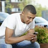 Nastolatek texting na jego wiszącej ozdobie Zdjęcia Royalty Free