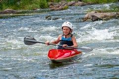 Nastolatek trenuje w sztuce kayaking Łódź na szorstkich rzecznych gwałtownych Dziecko zręcznie angażuje w flisactwie zdjęcie royalty free