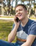 Nastolatek uśmiecha się opowiadać na telefonie komórkowym fotografia royalty free