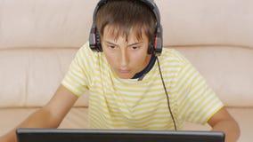 Nastolatek Używać Laptop Nastoletnia chłopiec poważnie patrzeje notatnika ekran naciska klawiaturę z hełmofonami zbiory wideo