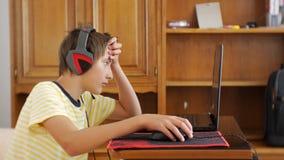 Nastolatek Używać Laptop Nastoletnia chłopiec z hełmofonami kleiącymi notatnika hazardu parawanowy używa komputerowy chrobot i my zbiory wideo