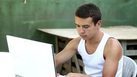 Nastolatek używa komputer w ogrodowym lato czasie zbiory