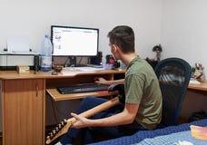 Nastolatek uczy się bawić się gitarę elektryczną Zdjęcie Stock