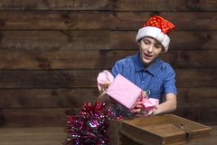 Nastolatek w Święty Mikołaj kapeluszu w błękitnej w kratkę koszula, szczęśliwie ciągnie out prezent od drewnianego pudełka z Boże zdjęcia stock